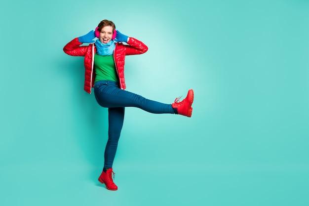 Foto a grandezza naturale di bella signora a piedi strada alza la gamba alta giocoso umore civettuolo mani sulle orecchie indossare casual cappotto rosso sciarpa rosa paraorecchie pantaloni maglione guanti scarpe isolato verde acqua muro di colore