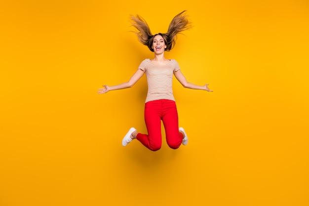 Foto a grandezza naturale di giocosa ragazza funky allegra avere tempo libero tenere la mano sentire l'espressione pazza saltare con il suo taglio di capelli cadere volare indossare maglietta stile casual isolato muro di colore luminoso