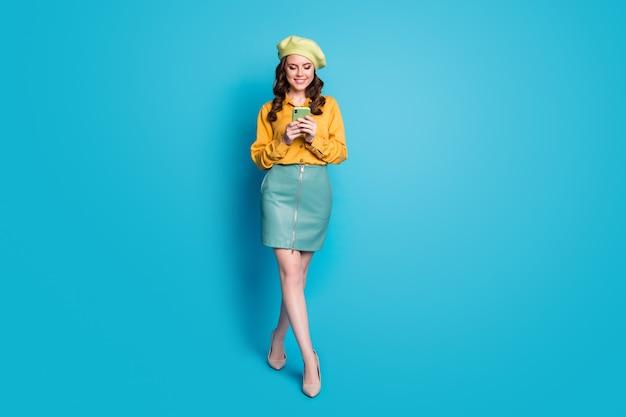 Foto a grandezza naturale della blogger ragazza positiva usa lo smartphone segui condividi commento notizie sui social network indossa tacchi a spillo gialli isolati su sfondo blu