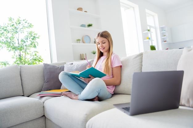 Foto a grandezza naturale di una ragazza positiva, seduta sul divano, gambe incrociate, studio remoto, scrittura, lezione, rapporto, quaderno in casa al chiuso