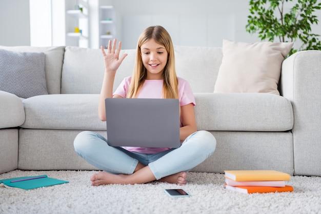 Foto a grandezza naturale di una ragazzina positiva, seduta sul pavimento, gambe incrociate, studio remoto, avere un computer portatile online, tutor, conferenza educativa, riunione, salutare in casa al chiuso