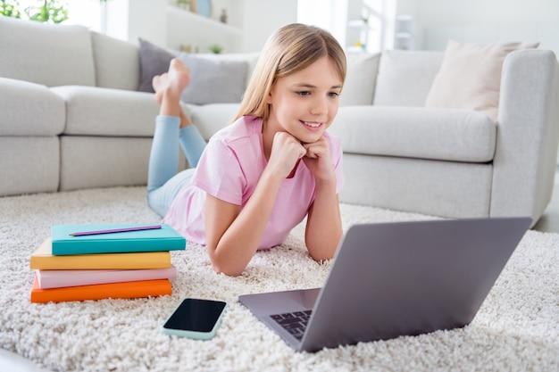 Foto a grandezza naturale di una ragazzina positiva che studia un computer portatile remoto guarda tutor educazione webinar sdraiato tappeto in casa al chiuso