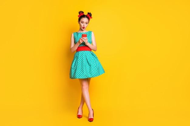 Foto a grandezza naturale di una ragazza sorpresa che usa il social network dello smartphone indossa una gonna verde isolata con uno sfondo di colore brillante