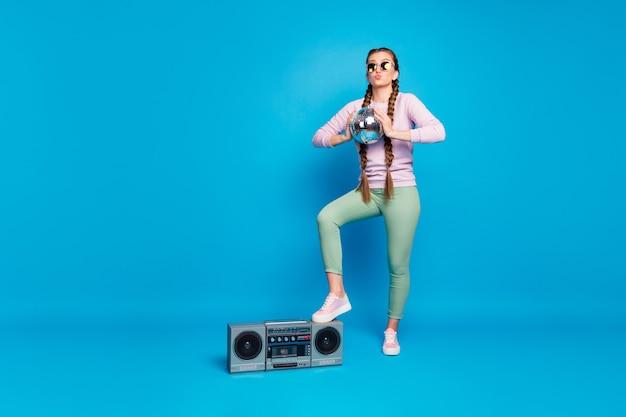 Foto a grandezza naturale di dolce ragazzina con le trecce rilassarsi nei fine settimana tenere palla da discoteca godersi l'evento mettere scarpe da ginnastica rosa su boombox indossare pantaloni verdi pullover isolato brillare sfondo di colore luminoso