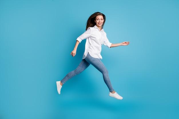 Foto del profilo a grandezza naturale di una donna attraente che salta in alto, indossa una camicia bianca, scarpe jeans, sfondo di colore blu isolato