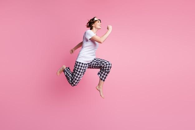 Foto di profilo a grandezza naturale della signora divertente che salta in alto e corre veloce