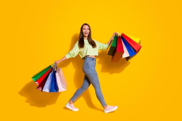 Foto del profilo a grandezza naturale di una bella donna maniaca dello shopping che cammina nel centro commerciale porta borse