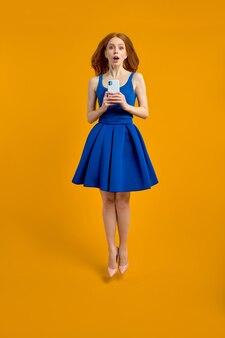 Foto del profilo a grandezza naturale di una donna rossa sorpresa in vestito che salta usa gli sconti per la ricerca dello smartphone funzionano velocemente sfondo giallo isolato nello spazio della copia del ritratto in studio per la pubblicità