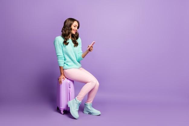 Ritratto di profilo a grandezza naturale di bella signora in attesa di registrazione in aeroporto sedersi borsa con ruote bagaglio navigazione telefono indossare soffici pullover rosa pastello pantaloni calzature.