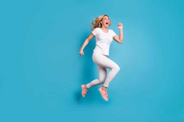 Full size profilo lato entusiasta pazza funky donna salto run
