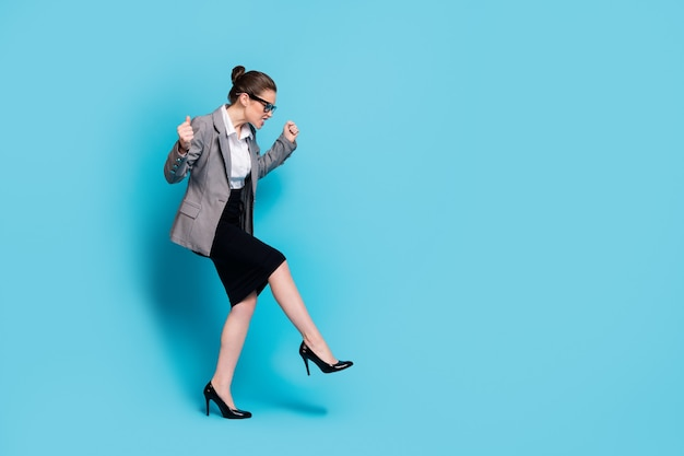 Foto a lato del profilo a grandezza naturale di una ragazza arrabbiata che alza i pugni calcia la gamba indossa una giacca blazer isolato sfondo di colore blu