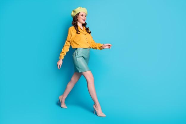 Profilo a grandezza naturale foto laterale di attraente dolce signora vai a piedi copyspace goditi il resto rilassati indossa un bell'aspetto vestiti scarpe copricapo isolate su sfondo blu