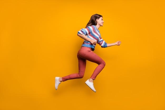 Foto laterale del profilo a grandezza naturale della corsa di salto della ragazza adorabile dei contenuti