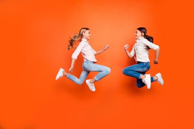 Foto laterale del profilo a grandezza naturale di due bambini divertenti positivi rilassarsi resto saltare correre giocare gioco indossare camicia bianca jeans jeans scarpe da ginnastica isolato sfondo di colore arancione