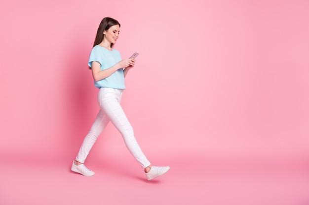 Foto a lato del profilo a grandezza naturale di una ragazza positiva che usa lo smartphone per andare in copyspace isolato su uno sfondo di colore pastello