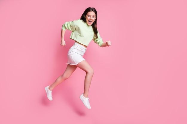 Foto a lato del profilo a grandezza naturale della ragazza energica sorpresa sentire sconti incredibili notizie saltare corri veloce indossare scarpe maglione alla moda alla moda bianco verde isolato su sfondo color pastello