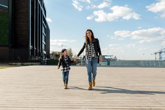 Fulllenght ritratto di famiglia della madre con la sua bambina che cammina fuori vicino al mare alla luce del sole