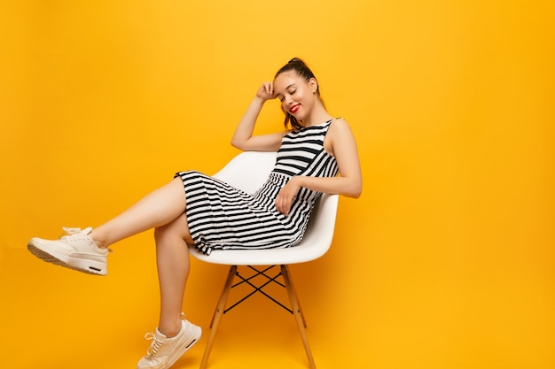 Fulllenght ritratto di donna piuttosto elegante che indossa scarpe da ginnastica bianche e abito spogliato in posa sul giallo