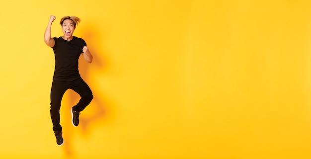 L'intera lunghezza di un ragazzo asiatico attraente e felice in abiti neri che salta e celebra la vittoria raggiunge go...
