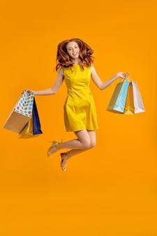 Ritratto a figura intera di donna carina rossa felice in abito giallo che salta divertendosi con lo shopping pac...