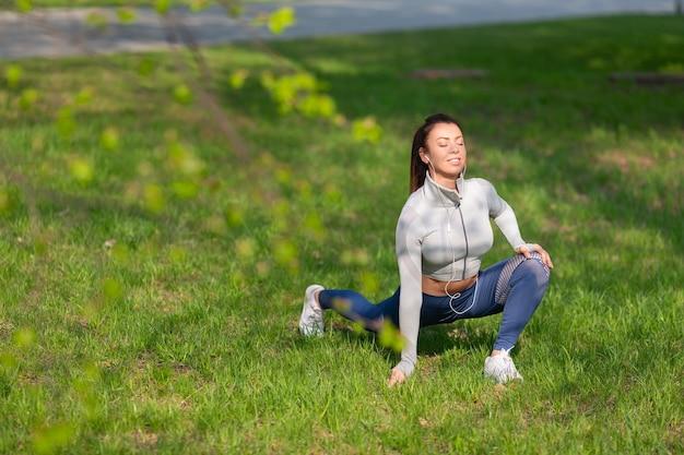 Foto verticale a figura intera della ragazza allunga i muscoli e si scalda prima della gara