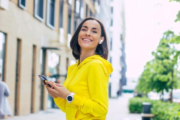 Completamente equipaggiato. ragazza sorridente in una felpa con cappuccio gialla, con una cuffia bluetooth nell'orecchio e uno smartwatch sulla mano sinistra, tenendo il telefono con entrambe le mani.