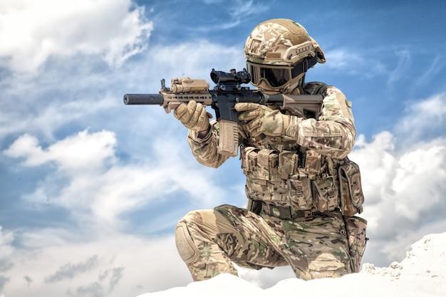 Completamente equipaggiato con munizioni tattiche giocatore softair in uniforme mimetica militare, mirando con mirino ottico sulla replica del fucile d'assalto di servizio mentre si sta su un ginocchio sullo sfondo del cielo nuvoloso