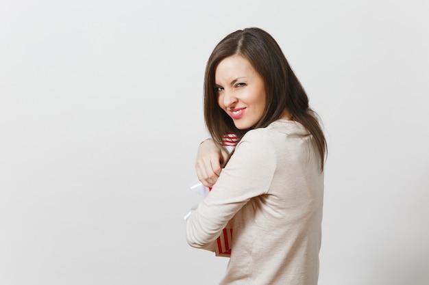 Divertente donna allegra che abbraccia scatola regalo a strisce rosse con nastro, fiocco isolato su priorità bassa bianca. per la pubblicità. san valentino, giornata internazionale della donna, concetto di festa di compleanno di natale.