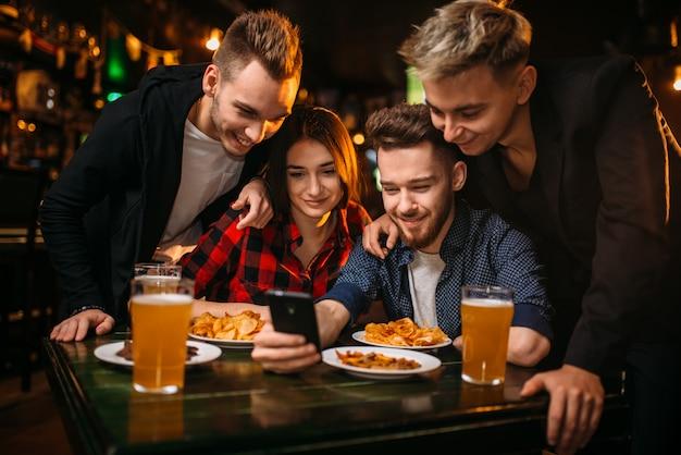 Una compagnia divertente guarda la foto sul telefono in un bar sportivo, tifosi di calcio felici