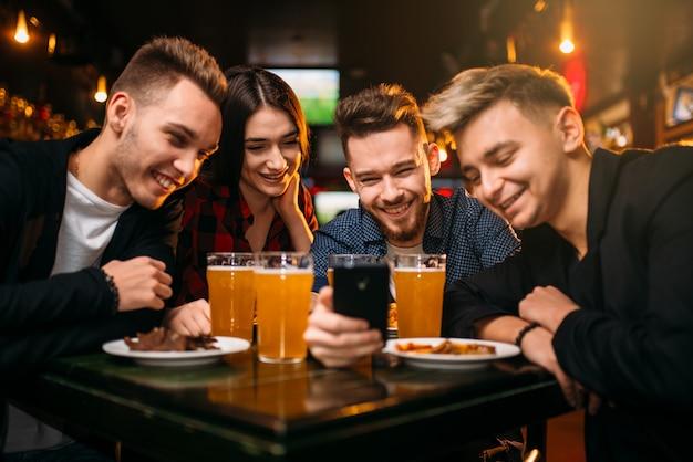 La compagnia divertente guarda la foto sul telefono in un bar sportivo