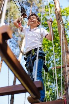 Esperienza divertente. affascinante ragazzo preadolescenziale che fa passi lungo il sentiero di corda e si diverte mentre sorride felice, godendosi l'altezza