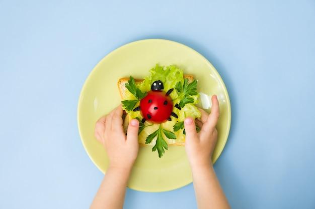Divertente arte culinaria per bambini. le mani dei bambini tengono il piatto con il panino della coccinella sulla parete blu. come preparare una colazione creativa per bambini a casa. istruzioni passo per passo, vista dall'alto