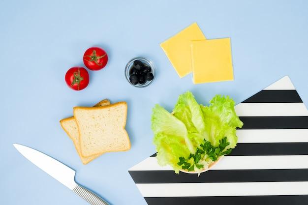 Divertente arte culinaria per bambini. panino di coccinella sulla parete blu. come preparare una colazione creativa per bambini a casa. istruzioni passo per passo, vista dall'alto. set di alimenti.