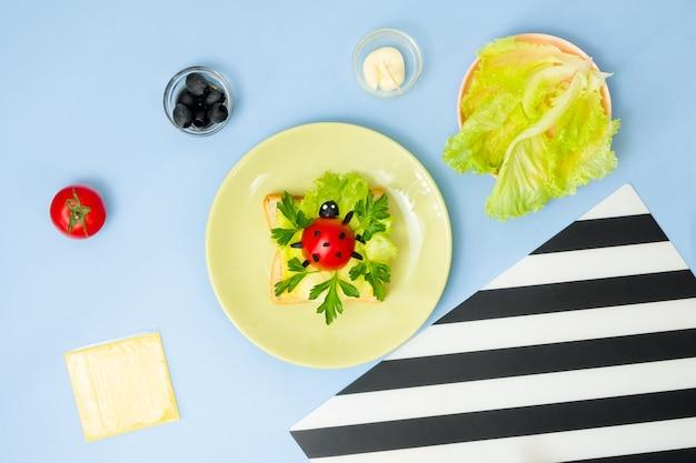 Divertente arte culinaria per bambini. panino di coccinella sulla parete blu. come preparare una colazione creativa per bambini a casa. istruzioni passo per passo, vista dall'alto. pasto pronto