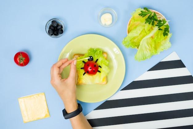 Divertente arte culinaria per bambini. panino di coccinella sulla parete blu. come preparare una colazione creativa per bambini a casa. istruzioni passo per passo, vista dall'alto.
