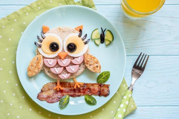 Cibo divertente per bambini - toast panino con gufo carino con salsicce e uova