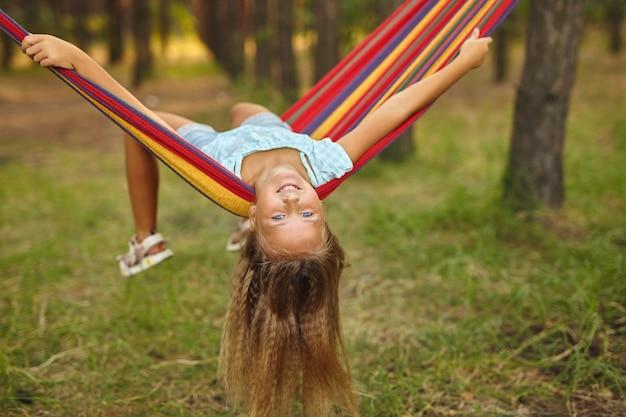 Divertimento in giardino per bambini che giocano su un'amaca colorata