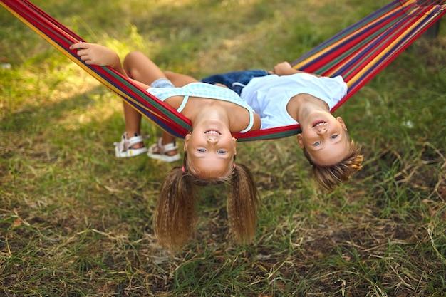 Divertimento in giardino. adorabili bambini che giocano su un'amaca colorata