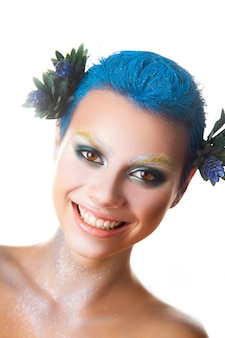 Ragazza divertente con trucco multicolore e breve acconciatura blu sorridente studio shot isolato
