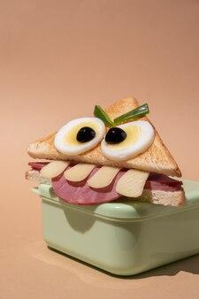 Divertente panino mostro di halloween con fetta di prosciutto, uova e formaggio