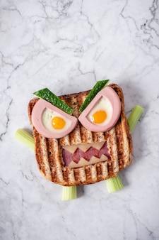 Divertente panino mostro di halloween con salsiccia di carne fetta, uova e formaggio sulla piastra