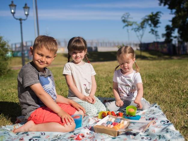 Divertimento bambini felici nel parco a una festa mangiando amaretto, picnic