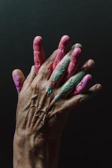 Tempo libero divertente. artista femminile creativo che mostra le mani sporche con vernice di colori diversi. sfondo scuro. concetti creativi artistici, immagine di bellezza