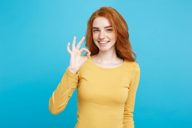 Divertimento e persone concetto headshot ritratto di affascinante zenzero rosso capelli ragazza con le lentiggini sorridente e facendo segno ok con il dito pastello blu parete copia spazio