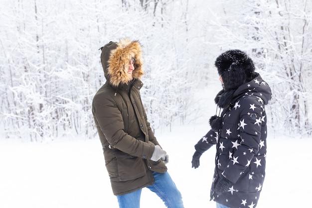 La stagione divertente e il concetto di svago amano la coppia che gioca a legno invernale sulla neve