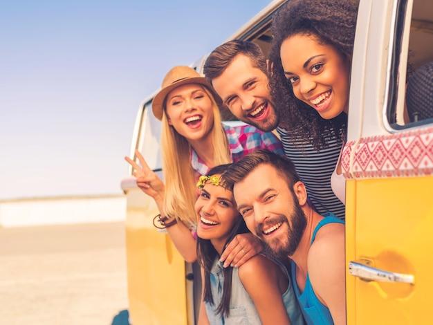 Tempo divertente con gli amici. gruppo di giovani felici che sorridono alla telecamera mentre sono seduti all'interno di un mini furgone retrò