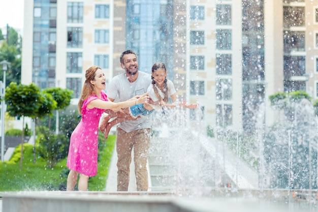 Momenti divertenti. genitori felici felici che giocano con la loro figlia stando in piedi vicino alla fontana