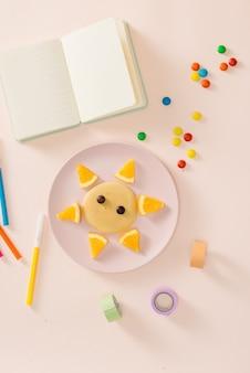Divertimento con il concetto di cibo - bambino che cucina e mangia una divertente colazione a base di leone pancake con arancia