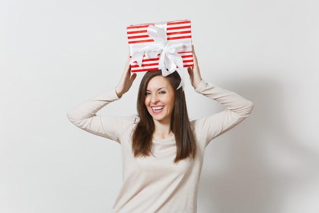 Donna divertente che tiene sopra la sua testa scatola regalo a strisce rossa con nastro isolato su sfondo bianco. per la pubblicità. san valentino, giornata internazionale della donna, compleanno di natale, concetto di vacanza