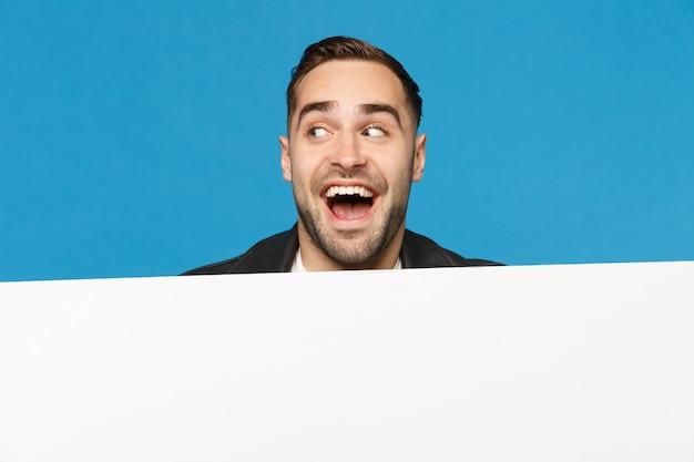 Il giovane uomo barbuto divertente guarda fuori il grande tabellone per le affissioni in bianco vuoto bianco per il contenuto promozionale isolato sul ritratto dello studio del fondo blu della parete. concetto di stile di vita di persone sincere emozioni. mock up copia spazio.